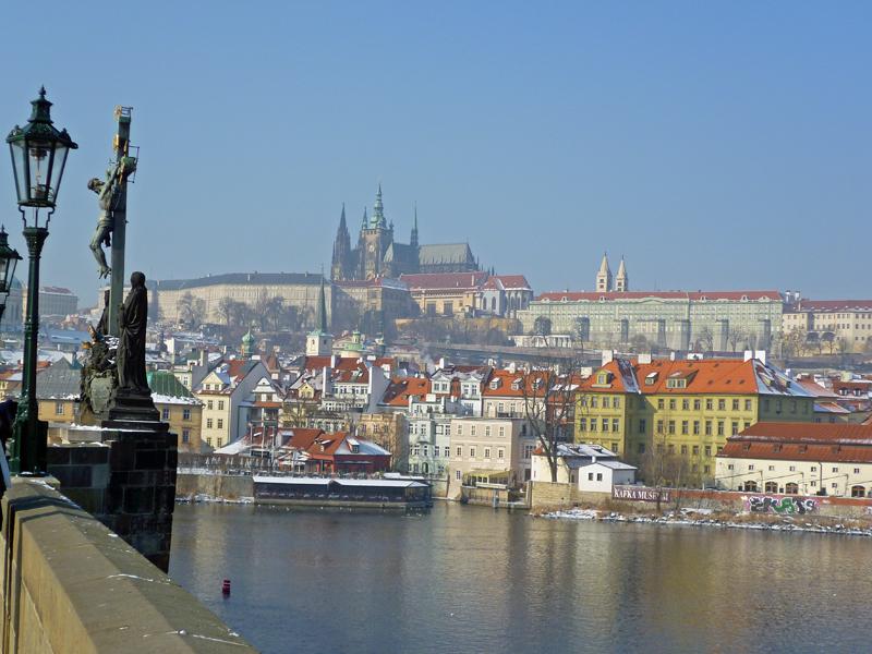 Blick von einer Brücke auf einen Stadtteil mit Hügel und Burg